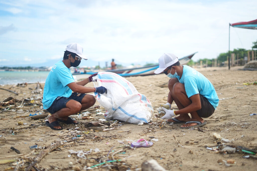 team members cleaning up a beach - team building